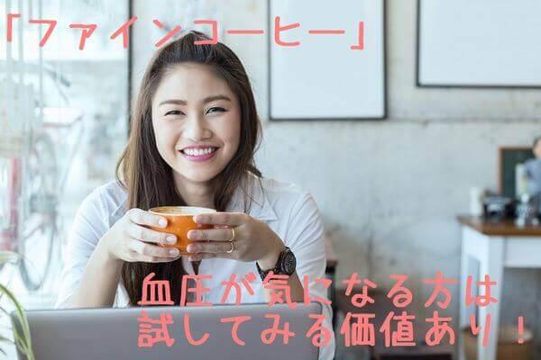 仕事中笑顔でコーヒーを飲む女性